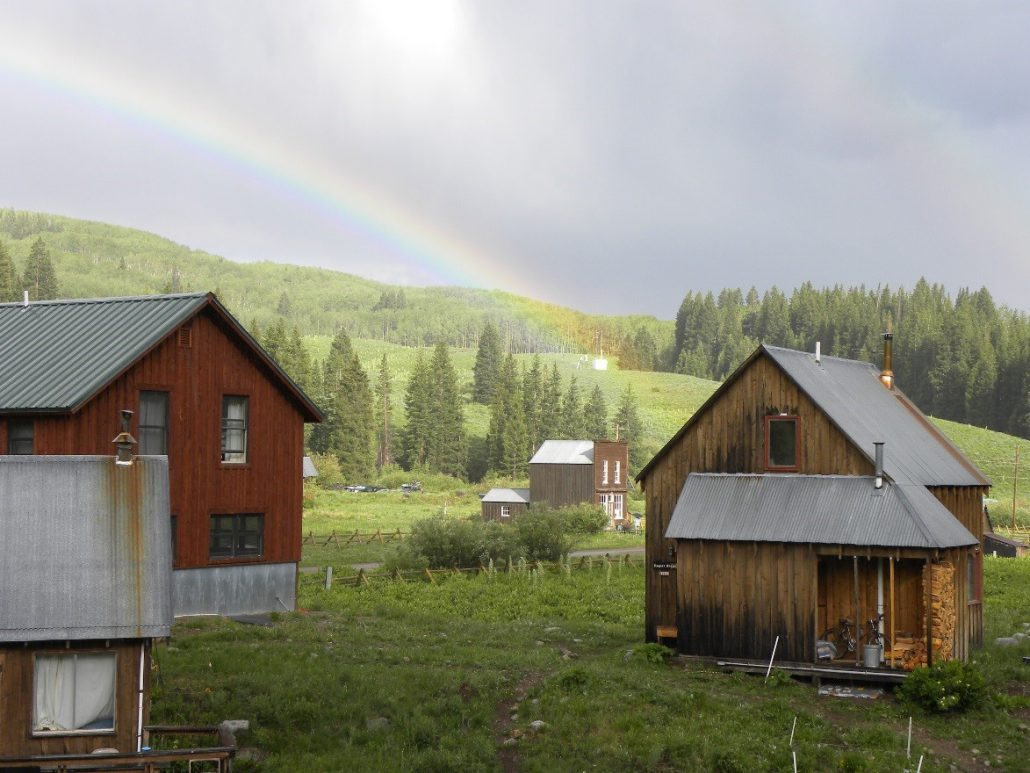 The town site of Gothic in 2010, crowned with a rainbow. The Rocky Mountain Biological Laboratory is a premier scientific research facility, set in an old silver-mining ghost town. A weather station sits up on the hill in the background.