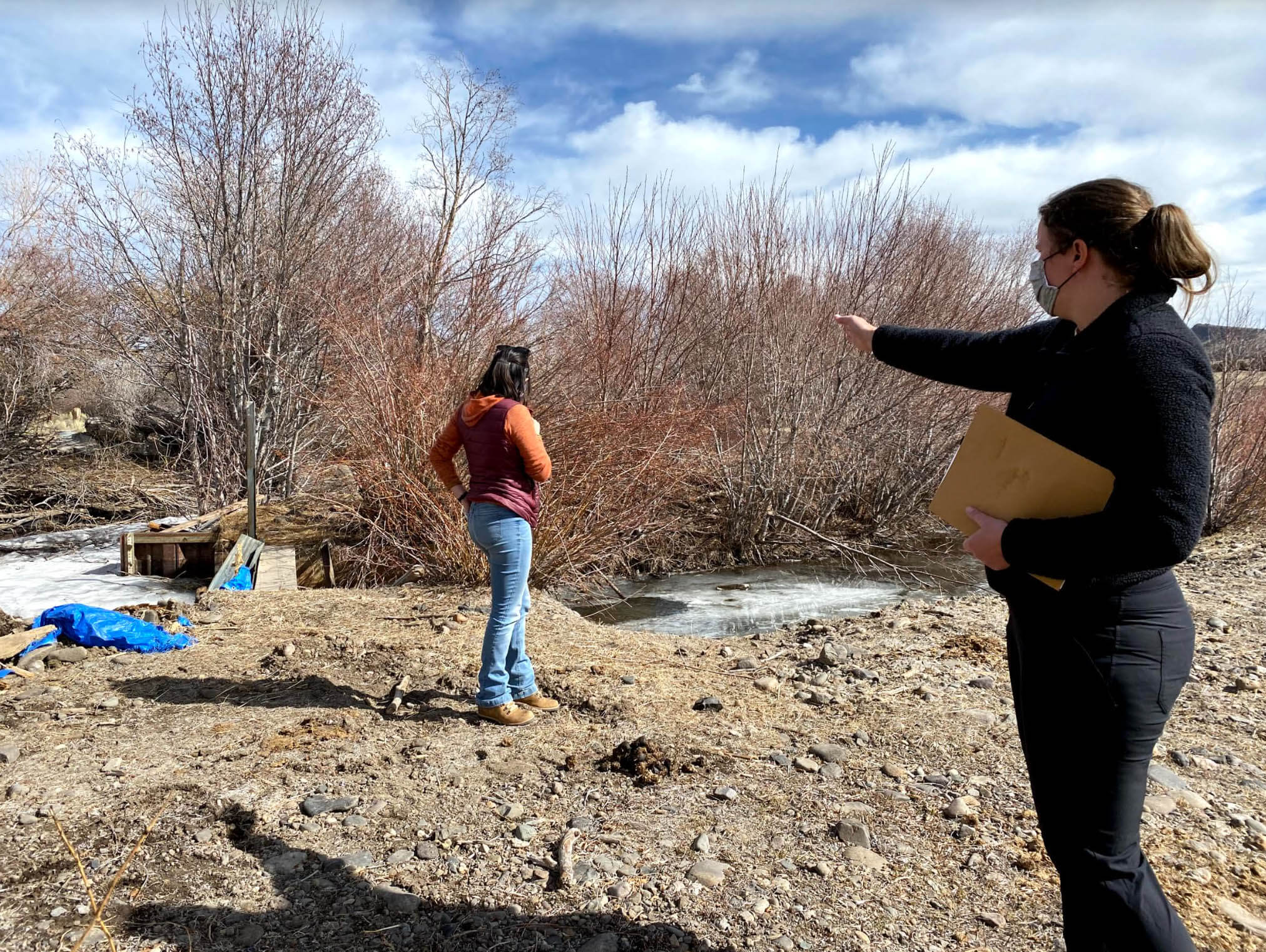 Emily (left) and Hallie Flynn (right) discussing the water control structure that needs to be replaced to better manage water flows to the meadows